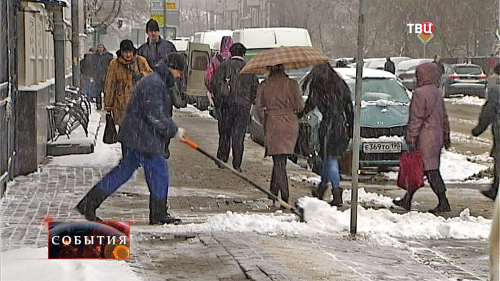 Дворник устраняет последствия снегопада в Москве