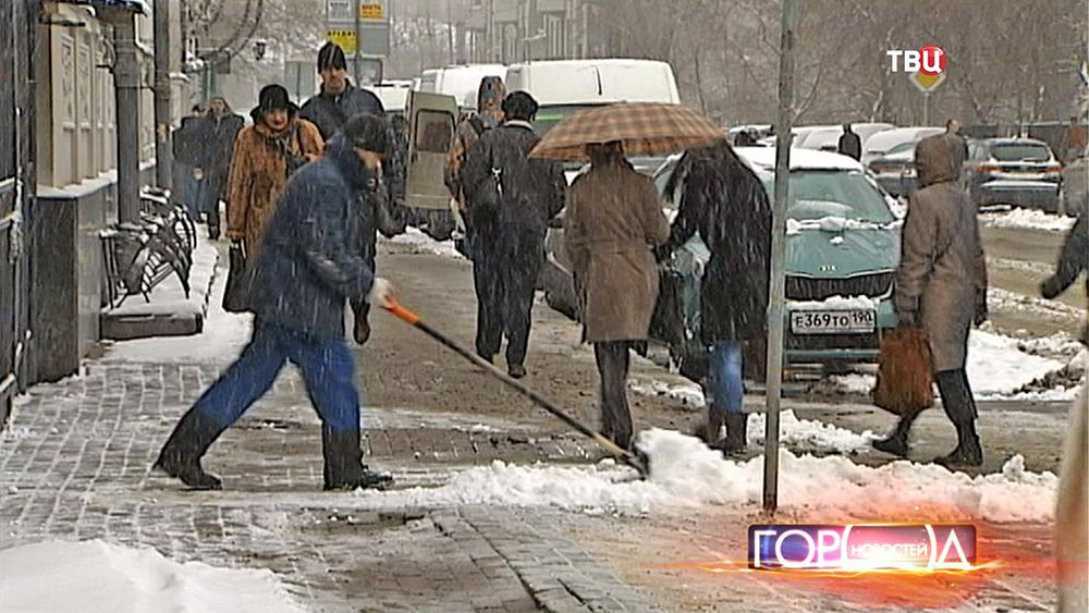 Дворник чистит тротуар после снегопада
