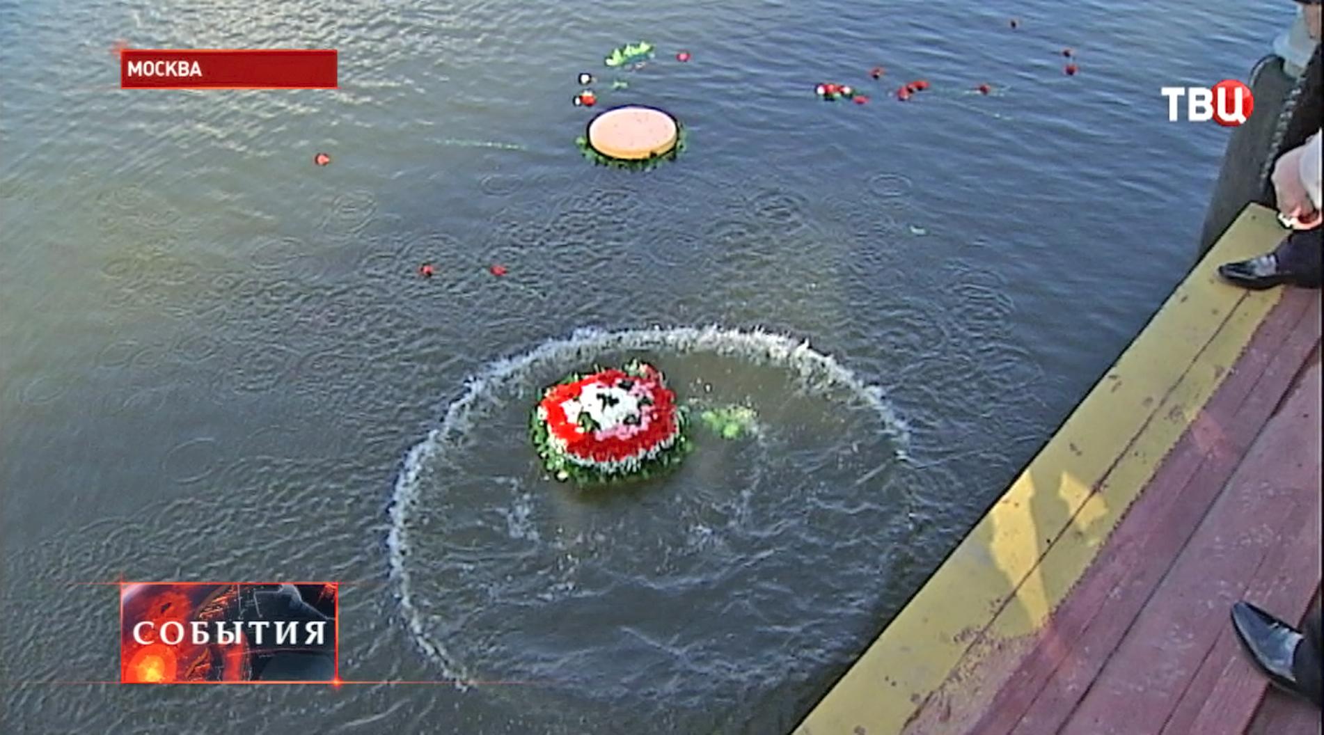 Люди кидают венки в память о погибших