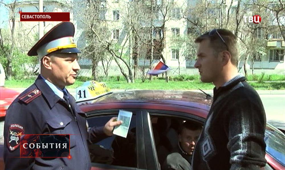 Инспектор ДПС Севастополя проверяет права у водителя