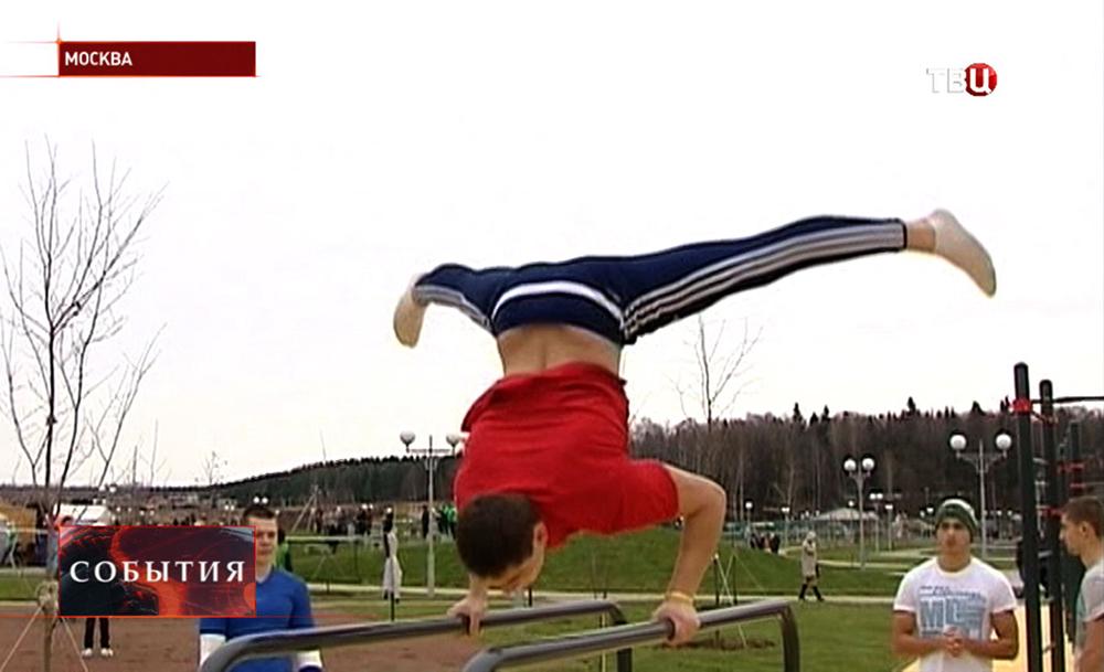 Спортсмен делает упражнения на перекладинах