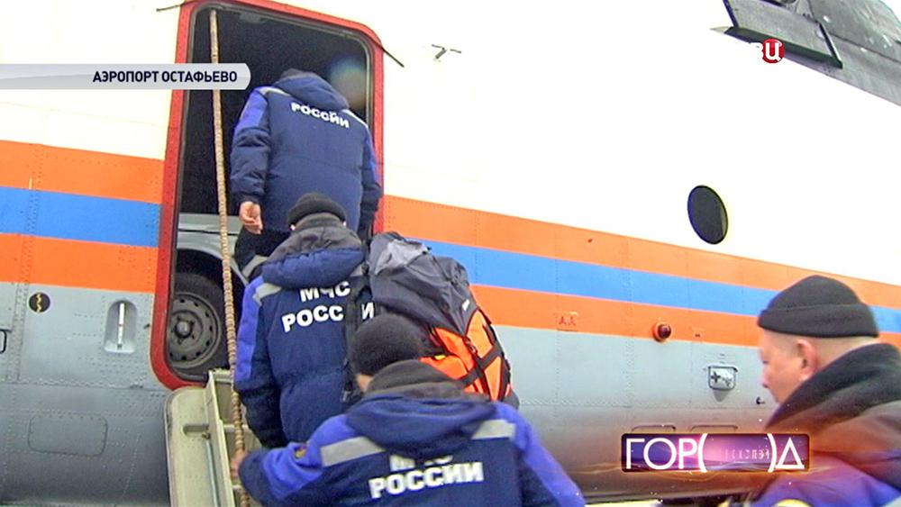 Спасатели МЧС заходят в вертолет