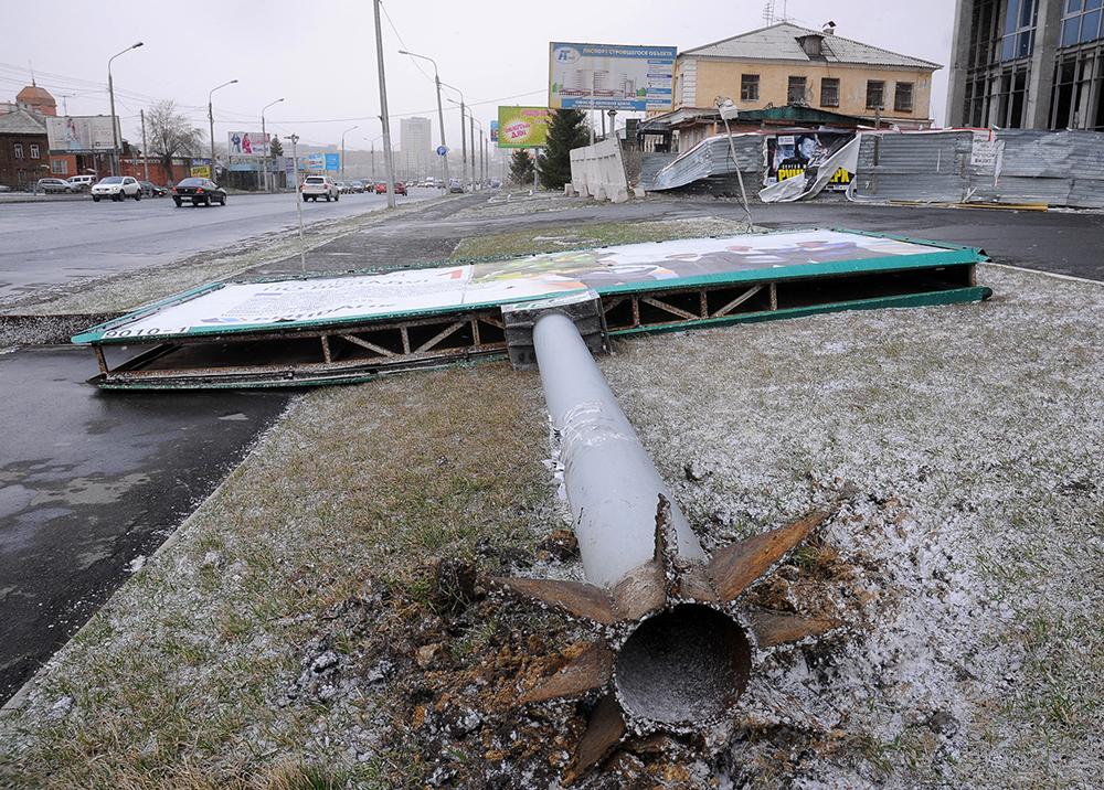 Рекламный щит, упавший от сильного ветра, на одной из улиц Омска