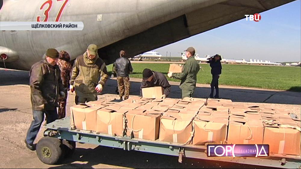 Метеоотряд грузит в самолет ящики с реагентом для разгона облаков